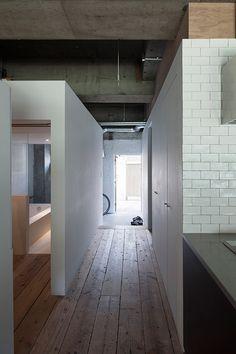 Plain white boxes contain rooms within the concrete skeleton of this Tokyo house.