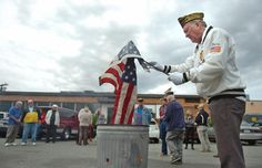 David Welch, an Air Force veteran, burns flags at the conclusion of a flag retirement ceremony at the Medford VFW.