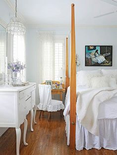 An inherited four-poster wood bed adds warmth to layers of white linens in this master bedroom. A secondhand pendant light sparkles over a curvaceous dresser; a white denim slipcover dresses a chair for a mix of pretty and practical./
