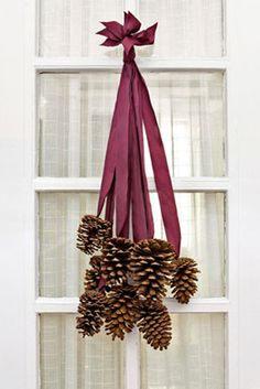 Instead of a wreath, hang these pretty pinecones from your door to welcome the season.