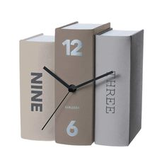 This sensational clock will have book lovers swooning with delight. When you just can't get enough books, get a clock that is made up of books! Three authentic looking tomes entitled, Three, Nine and 12 / 6 stand together forming the body of this creative clock. The sophisticated shades of tan and grey will blend perfectly into a home or office library. Time is indicated by a set of elegant black hands. The ultimate gift for any bookworm! Size H20cm x W15cm x D20cm.