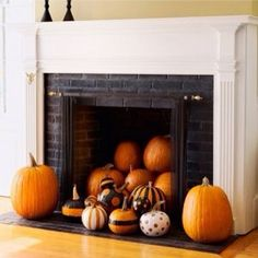 Pumpkins decorate an unused fireplace for Thanksgiving.