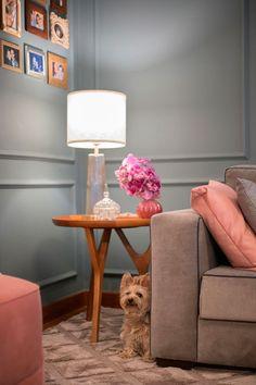 Decoração de apartamento com estilo romântico. Parede cinza, sofá cinza, sofá rosa, mesa lateral, mesa de apoio, luminária de mesa com vaso rosa com flor, quadrinhos. #decoracao #decor #details #casadevalentina