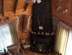 Otro estilo de estufa hogar en un estar de una cabaña de troncos macizos. La masa térmica de paredes de troncos constituye un excelente medio de conservación de energía (calórica y de enfriamiento). Mas detalles en nuestra pag. web: casadetroncos.com