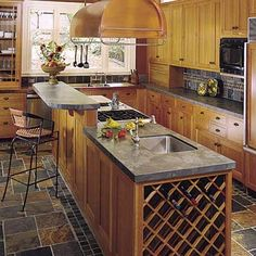 This large, narrow island features an entertaining zone with wine storage near a prep sink, and a raised  breakfast bar or staging area that conceals the chef's lower workstation and cooktop. | Photo: David Duncan Livingston | thisoldhouse.com