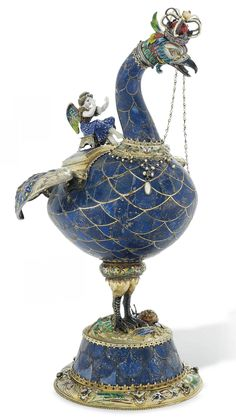 AN AUSTRIAN SILVER-GILT-MOUNTED AND ENAMELLED MODEL OF A BIRD  MARK OF HERMANN BOHM, VIENNA, LAST QUARTER 19TH CENTURY  Realistically modelled, the lapis lazuli body set is panels to simulate feathers, with raised wings and tail, the back with detachable cover with finial cast and enamelled as a winged putto, with gilt-metal liner, the head set with a pearl-set crown, the circular base applied with enamelled reptiles and insects on a ground cast as rockwork, marked on foot, base
