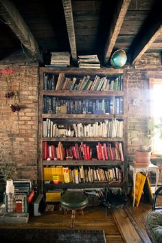 old color coded bookshelf with brick wall