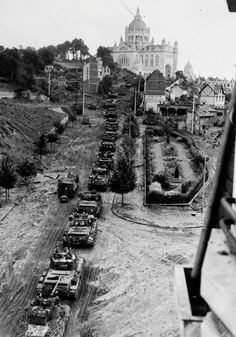 A column of Cromwell and Sherman Firefly tanks of 1st RTR 7th Armoured Division enters Lisieux 23 or 24 August 1944. In the background is the Basilica of St Therese.