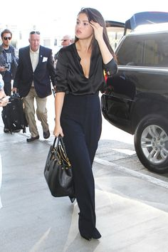 Selena Gomez in a black silk blouse and high waist trousers