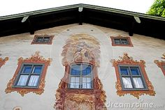 Photo made in Oberammergau in Bavaria (Germany). The picture shows the facade of one of the typical houses of the country where almost all the houses are painted and some with scenes depicting fairy tales. In the picture you see three windows with white curtains, in particular the central window is in the middle of a large fresco.