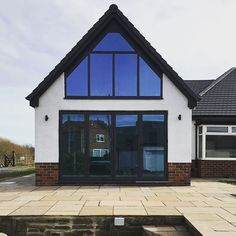 Gable End Aluminium Bi-Folding Doors & Angled Frame Windows in Anthracite Grey on a beautiful rendered home with Pilkington K Active Blue Glass with Heat Reflection Supplied & Installed by National Window Systems. Contact us for a quote on 01325 381630 o Bungalow Conversion, Loft Conversion Bedroom, Bungalow Exterior, Bungalow Renovation, Bungalow Ideas, Bungalow Extensions, House Extensions, Gable Window, Rear Window