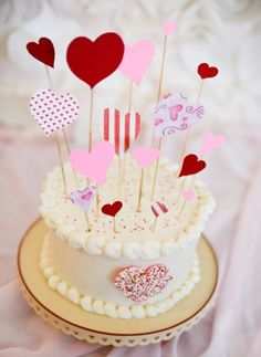 Scrapbook paper, wooden skewers, and a little glue (or even  just tape!) make a perfect Valentine's day cake topper in a flash.