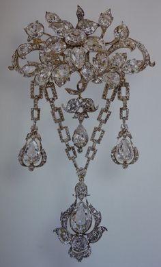 The Duchess of Teck`s Diamond Flower brooch. This brooch was made about mid 1800s from diamonds, silver & gold. It belonged to Princess Mary Adelaide, Duchess of Teck (Queen Mary`s mother) It was left to Queen Mary`s brother in 1897 but  Queen Mary had come into possession of it by 1923, when she gave it to her son, the Duke of York as a gift for his bride Lady Elizabeth Bowes Lyon. It remained a favourite brooch of the Queen Mother`s for the rest of her life.