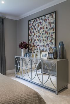 Stunningly crafted, this bespoke mirrored sideboard radiates elegance and sophistication within our Kirkby Homes Hartley Wintney master bedroom design, whilst the large colourful painting injects convivial warmth to the grey hue of the room. #interiordesign #sideboard