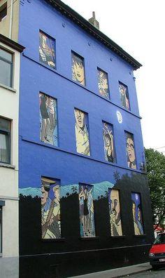 """-place de Ninove 10-La fresque murale bruxelloise de Caroline Baldwin d'après un projet original d'André Taymans fut inaugurée en septembre 2003.Sortant du modèle habituel des fresques BD qui reproduisent un seul dessin, celle-ci se présente comme une suite d'illustrations sur fond de ciel étoilé. Seize niches dans le mur emmènent le spectateur dans un hommage à l'aventurière plein de couleur et d'atmosphère. Réalisation  société """"Art Mural"""". Le coloriage est l'oeuvre de Bruno Wesel."""