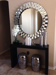 I want an entryway set up similar to this. The theme I am aiming for is shades of grey, white, and silver/mirrored so this would fit in perfectly. I would get a mirror similar to this one, and nice grey shelf with some nice accent decor for the top just like here. I also really like the idea of the silver stools for people to sit on to put on shoes etc. This is the first think people see when they walk in so i'd like to make it look pretty but not to crowed.