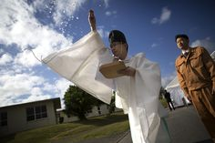 Shinto priest Nobuhiko Tsuji purifies the grounds by throwing shreds of paper during a groundbreaking ceremony on U.S. Marine Corps Camp Foster, Jan. 15, 2015.