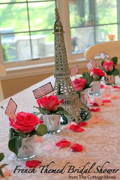 FRENCH THEMED BRIDAL SHOWER.  Black Eiffel Tower with vases of flowers and votive candles surrounding it on a round table.