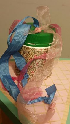 DIY Baby ribbon tug toy. You need: an empty container with holes drilled in the lid, material to cover the outside and colourful ribbons.