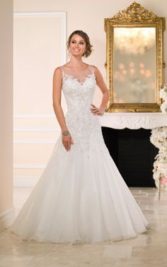 Read more on this organza fit-and-flare wedding gown from the Stella York bridal gown collection with sparkling crystal buttons and an illusion high neckline and back.