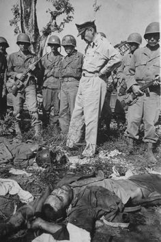 General Douglas MacArthur looking at bodies of Japanese soldiers killed hours before during the fight to take Bataan and liberate the Philippines from Japanese occupation. Location: Bataan, Philippine Islands  Date taken: February 16, 1945  (Life Magazine photo)