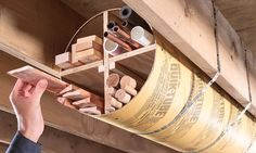 solution for storing things like wood trim, edge banding and pipes. 12-in.-dia. by 8-ft.-long cardboard concrete form, add plywood dividers and hang it from the ceiling with plumber's strap.