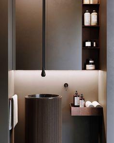 Com tons terrosos, o arquiteto Max Chapliuk usou materiais que vão do cobre ao mármore para reforçar a atmosfera sóbria do banheiro. O volume da pia é o grande protagonista, recebendo ainda a divertida torneira vertical!
