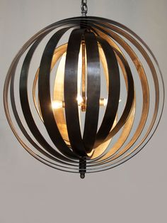 subtly spiraled, concentric metal bands encircle a central 4 bulb candelabra, which radiates warm light from its core. geometric elegance in 3D form, the cosmos candelabra is a sophisticated lighting choice for any room in the home.