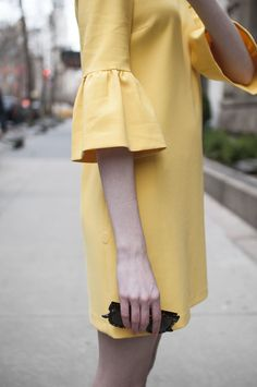 yellow ruffle bell sleeve dress, bright pink earrings, striped socks with block heeled ankle strap sandals