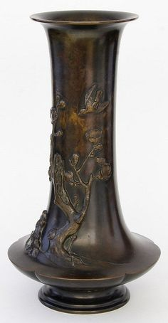 A Japanese relief cast bronze vase, Meiji period (1868-1912), of flattened baluster form rising from a stepped spreading base, cast in high relief with flowering blossom trees with birds in flight, unsigned, 34cm high