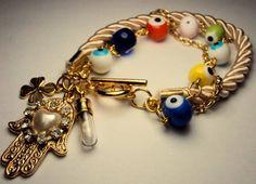 Lindíssima pulseira com cordão de seda, olhos gregos coloridos e pingentes de trevo, sal grosso e mão hamsa. R$ 39,00