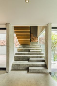 Stairs at lumber Shaped-Box House in Jakarta, Indonesia by Atelier Riri