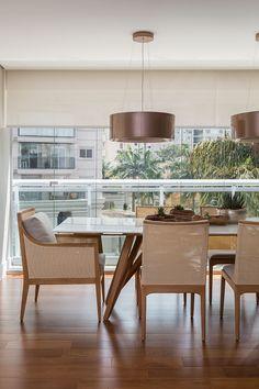 Decoração de apartamento moderno e integrado. Na mesa de jantar retangular branca, com vaso de planta, adornos e luz natural.