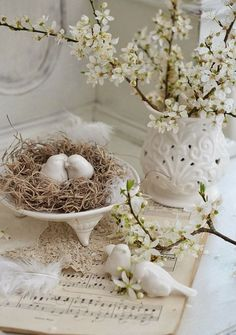 White ceramic birds nesting, sheet music , white blossom. Styling.