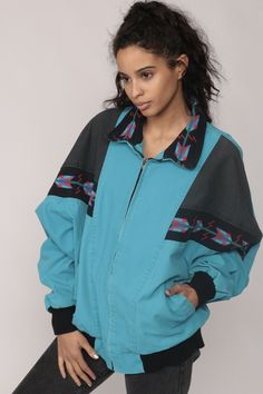 """Vintage 80s 90s jacket in turquoise blue with tribal trim and raglan sleeves and a fleece lining. Zips up the front. Unisex.  Every item we sell is authentic vintage and one-of-a-kind! You will receive the EXACT item shown in the photos. For reference, model is 5'7"""" and measures 32-23-35. DETAILS  Best fits: Large to Extra Large (Note: We only have ONE in stock. If more than one size is listed it is because this item will work on a range of sizes. Check measurements for exact fit.)…"""