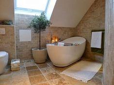 Mediterranes Badezimmer mit freistehender Badewanne. Dachschräge in Szene gesetzt.