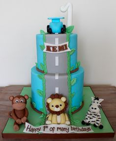 Safari and race car first birthday cake with fondant edible figurine monkey lion zebra