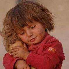 This Syrian girl is closing the eyes of her doll, because she does not want her doll to see what she saw.