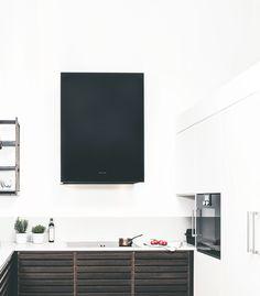 Ett modernt, minimalistiskt kök med rustika trädetaljer. Den vita, fräscha basen bryts av med en svart fläktkupa som genom sin enkla design ger köket en estetiskt tilltalande look. #fjaraskupan #box #minimalism #modernt #enkelhet