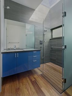 A custom skylight floods the bathroom with light. A tempered glass shower and Grohe faucet accent the space; custom glossy cabinetry with Hafele hardware again adds a pop of color. Tagged: Bath Room, Medium Hardwood Floor, Undermount Sink, Enclosed Shower, Full Shower, and Stone Tile Wall. Photo 6 of 8 in An Indoor-Outdoor Renovation for a 1950s Ranch House in the Bay Area from 1950s Ranch