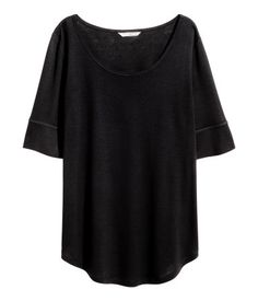Black. Top in soft, gently draping jersey with elbow-length sleeves and a rounded hem.