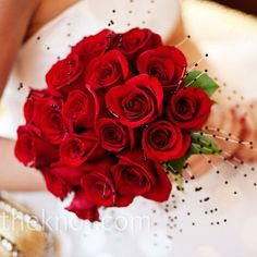The bride carried a red rose bouquet with clusters of small black pearls throughout. The stems wrapped in black satin ribbon.
