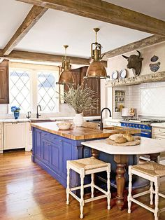 Salvaged Charm This blue-painted island is topped with a butcher-block countertop that was pieced together from small squares cut from farmhouse beams. World War II-era ship lanterns suspend over the island and marble tabletop, keeping in step with the kitchen's antique charm. Different wood tones used throughout the kitchen give the appearance of a room that has evolved over time.
