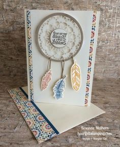 Looks like this is made with circle die, doily and feather stamps.