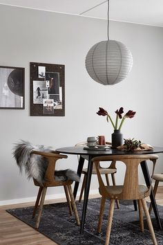 Stylish and elegant dining room with a round glass table, some wooden chairs, a fake fur and a small gallery wall.