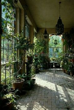 Plant filled Boho sunroom, with beautiful Bohemian style lanterns and awesome brick floor!