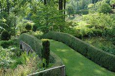 A bridge covered in grass and using short boxwood hedging as its railing is the focal point of the Jardin de Berchigranges