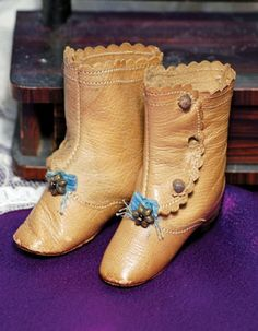 """2 ¼"""" l, 2 ½"""" h, camel-tan leather boots with metal star decoration and tiny blue bows, leather soles, brown wooden heels, side-button closing."""