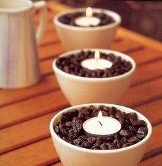 Potinhos de louça cheios de grãos de café com velas de rechaud.