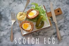 scotch egg - soft boiled egg encased in a homemade sausage mix; dredged in flour, dipped in egg, and then rolled around in breadcrumbs and deep fried! crispy exterior, soft yolk, served with spicy dijon and cornichons. the ultimate breakfast.